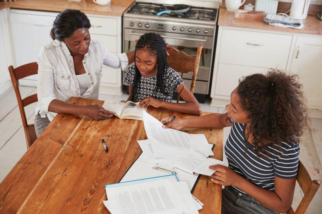 Moeder meisjes huiswerk keuken